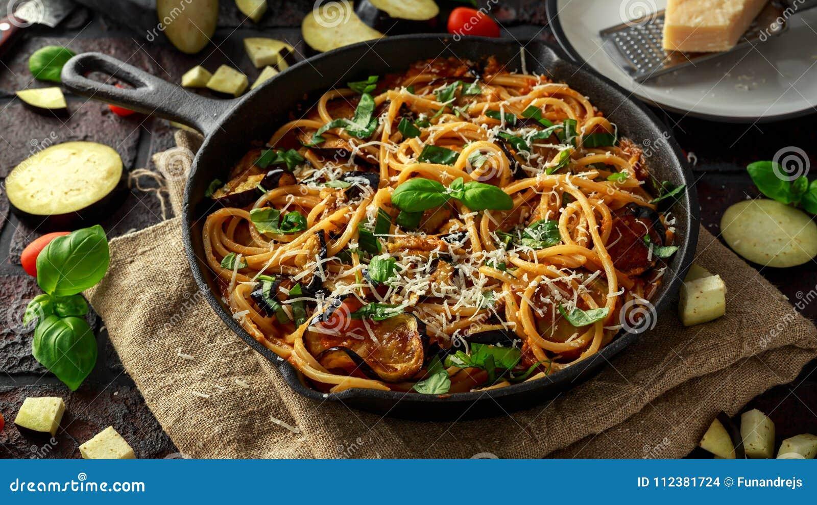 Vegetarische Italiaanse alla Norma van de Deegwarenspaghetti met aubergine, tomaten, basilicum en parmezaanse kaaskaas in rustiek