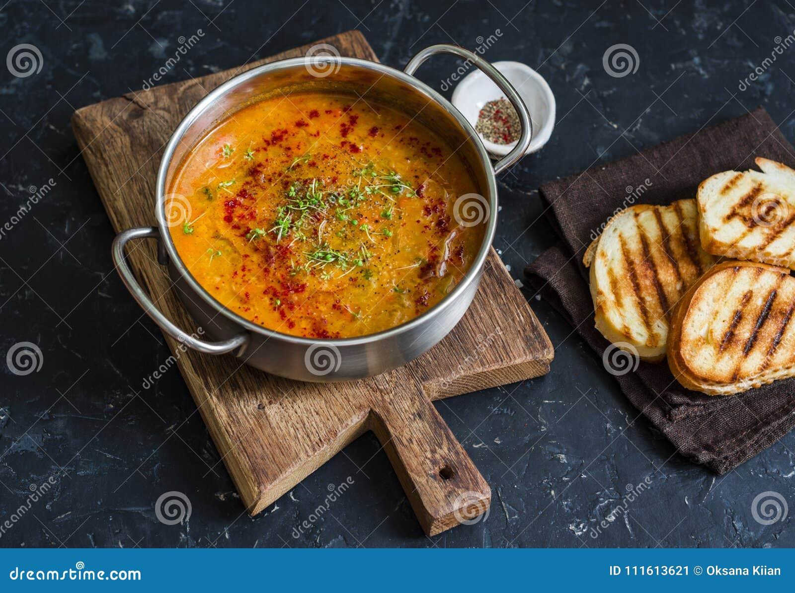 Vegetarische Linsensuppe des geräucherten Paprikas mit gegrilltem Käse schiebt einen dunklen Hintergrund, Draufsicht ein Köstlich