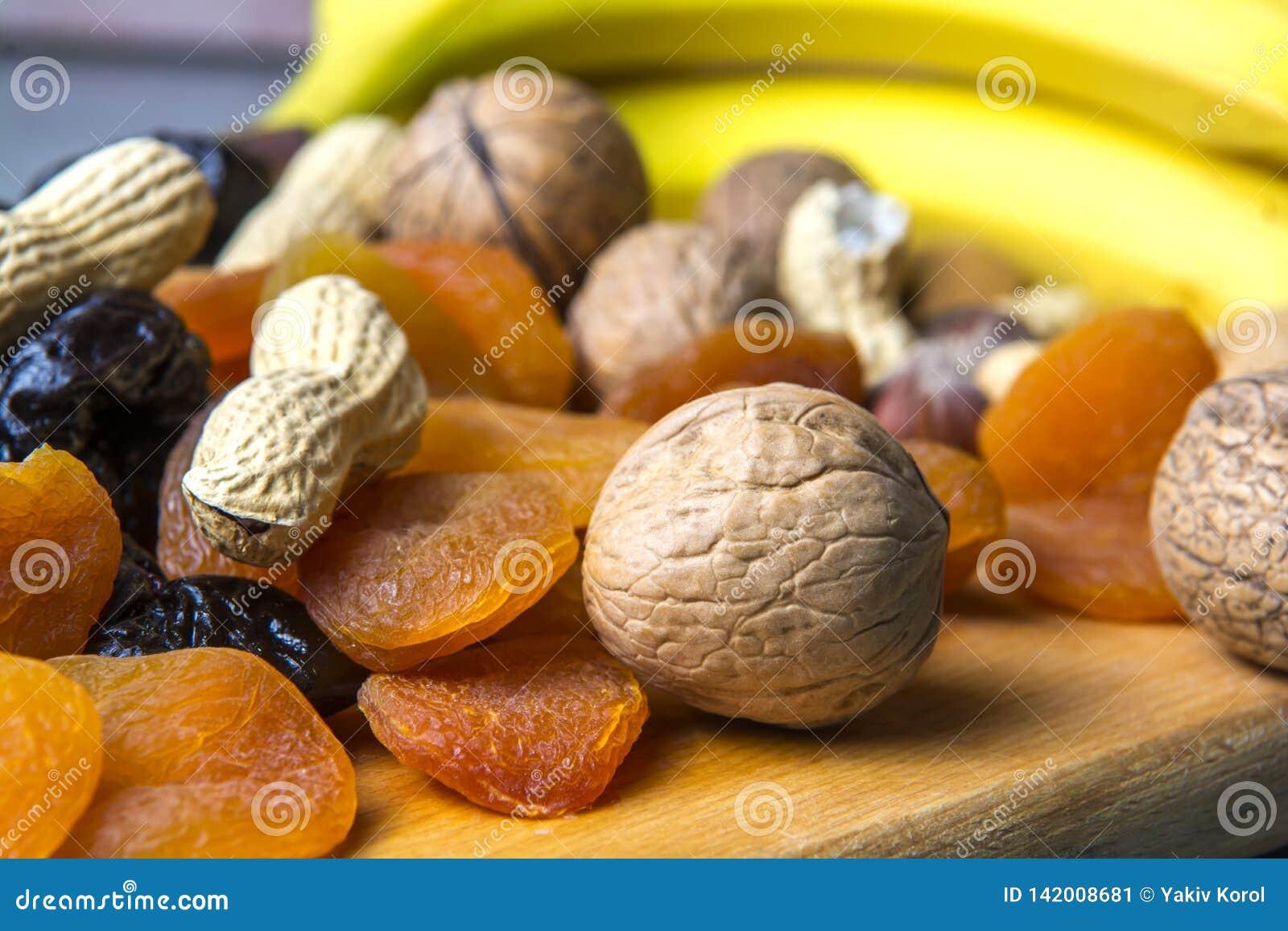 Vegetarische Nahrung von Nüssen und von Trockenfrüchten auf dem Küchenbrett