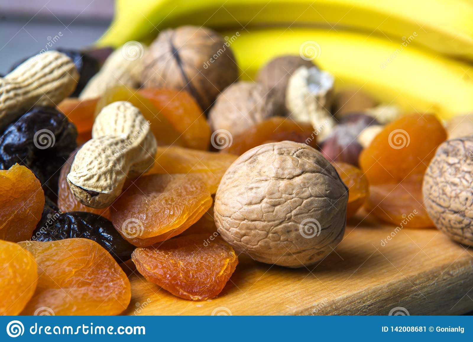 Vegetarisk mat av muttrar och torkade frukter på kökbrädet