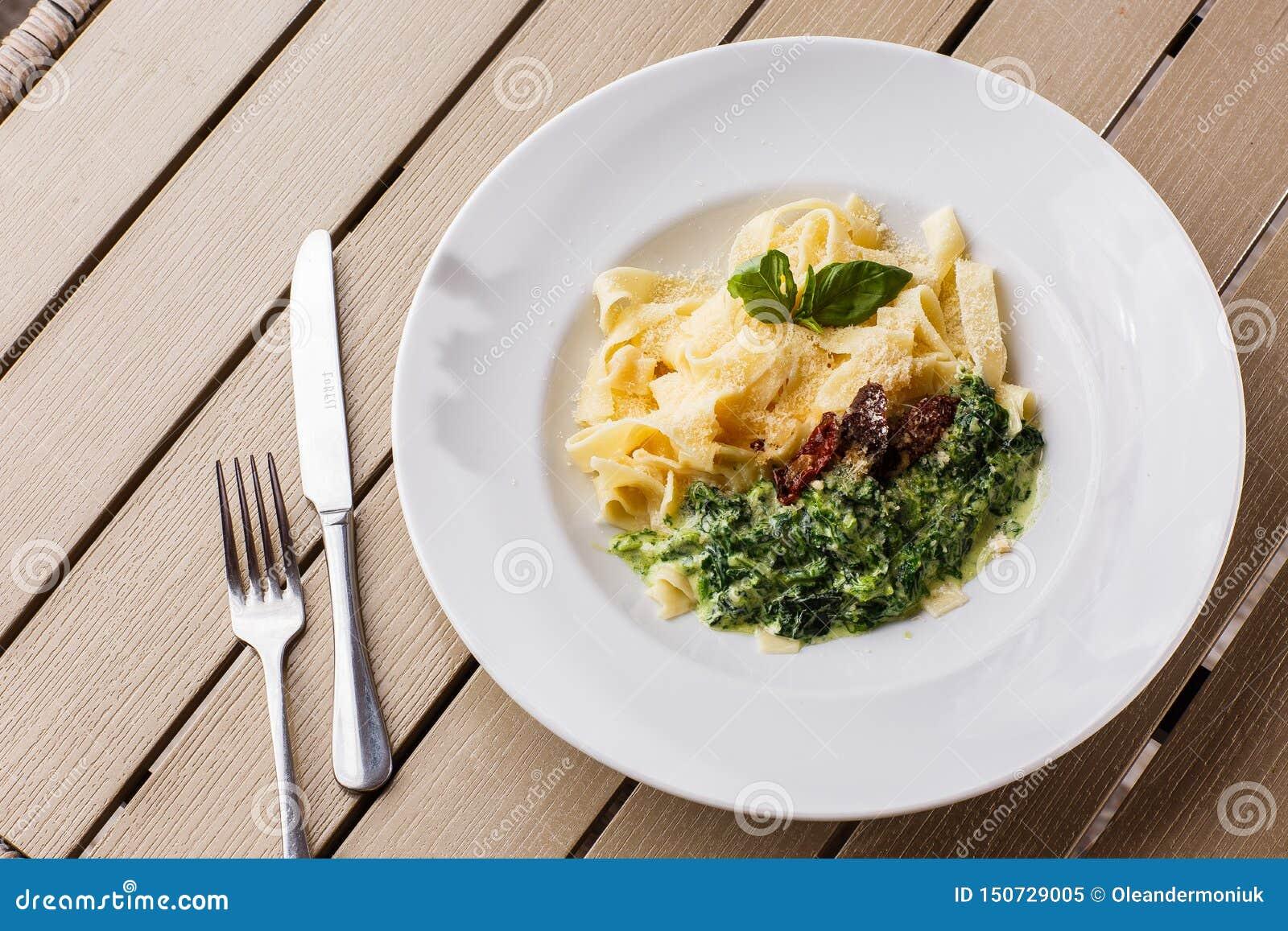 Vegetarisk pastamaträtt för tagliatelle med spenat och torkade tomater som dekoreras med basilika Läcker lunch med pasta och