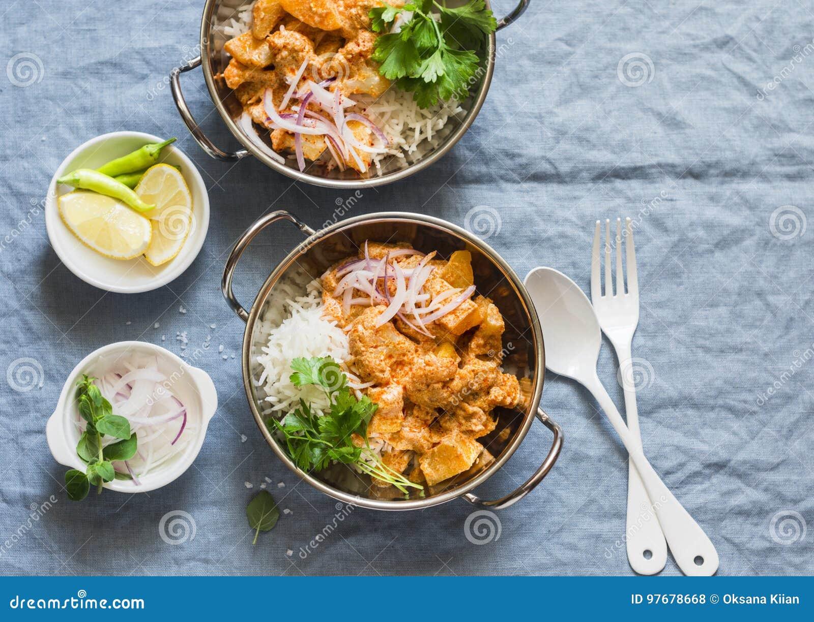 Vegetarisk potatis- och blomkålcurry med ris i currydisk på en blå bakgrund, bästa sikt Vegetariskt sunt matbegrepp