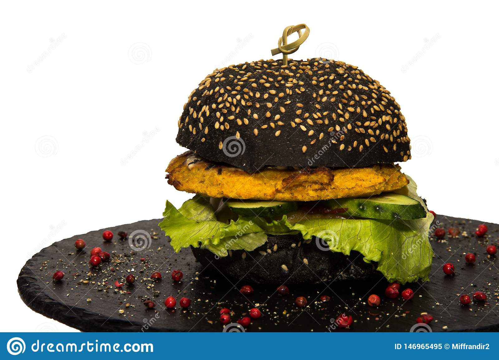 Veggie black hamburger with green salad and cucumber. Isolated on white