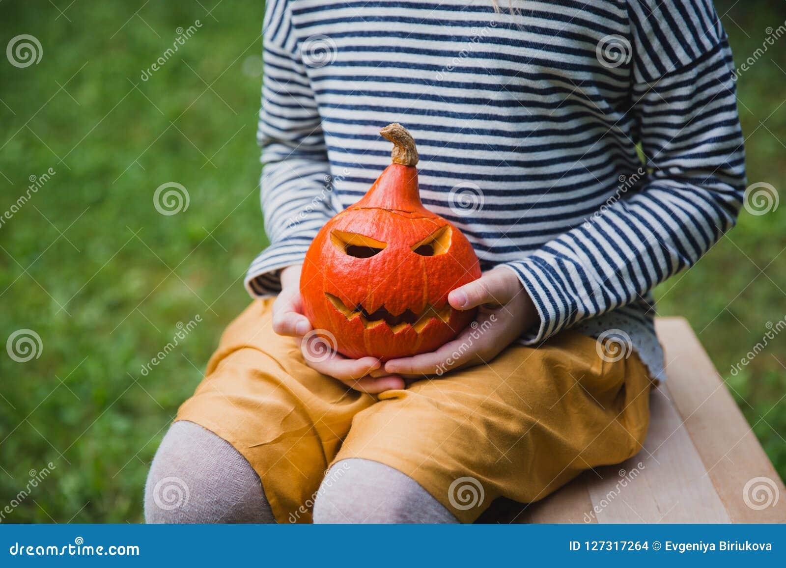 Veille de la toussaint heureuse Sièges de fille sur la chaise et les prises en bois peu de lanternes de Jack O de potiron dehors