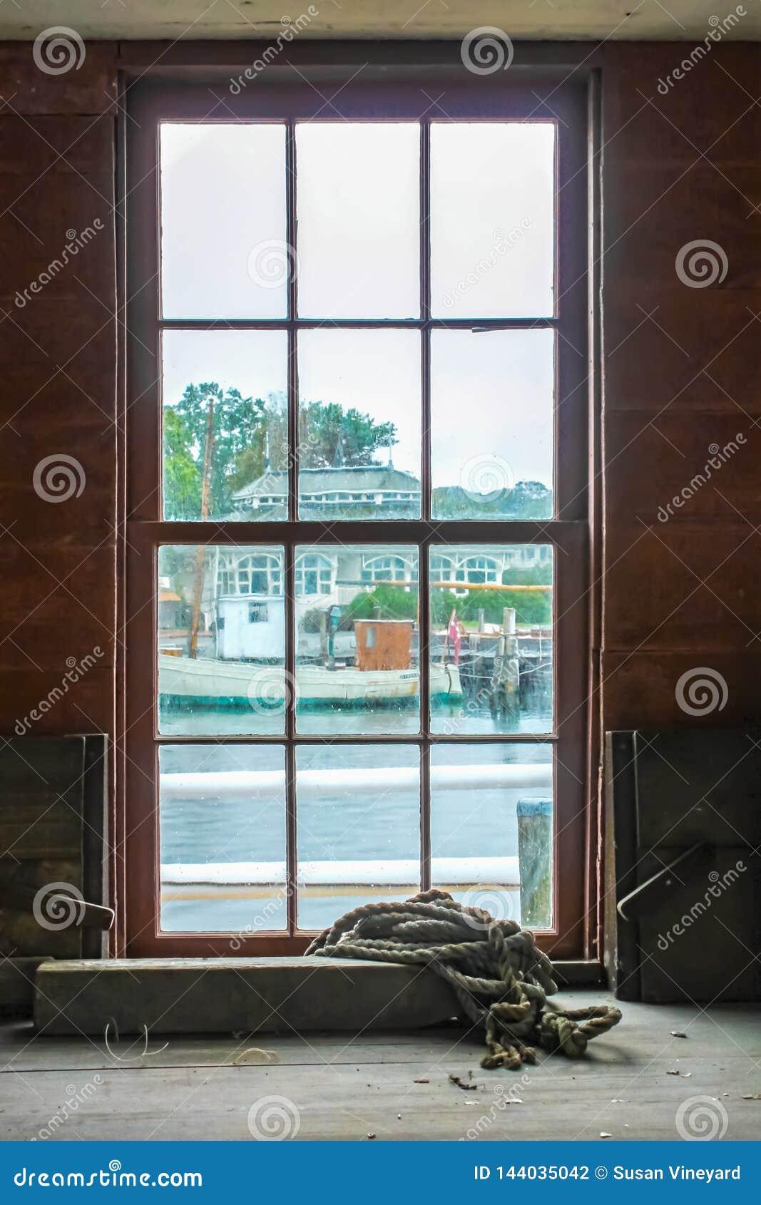 Veja para fora a janela paned suja suja no dia chuvoso da construção da oficina com a corda que coloca em uma prateleira a outras
