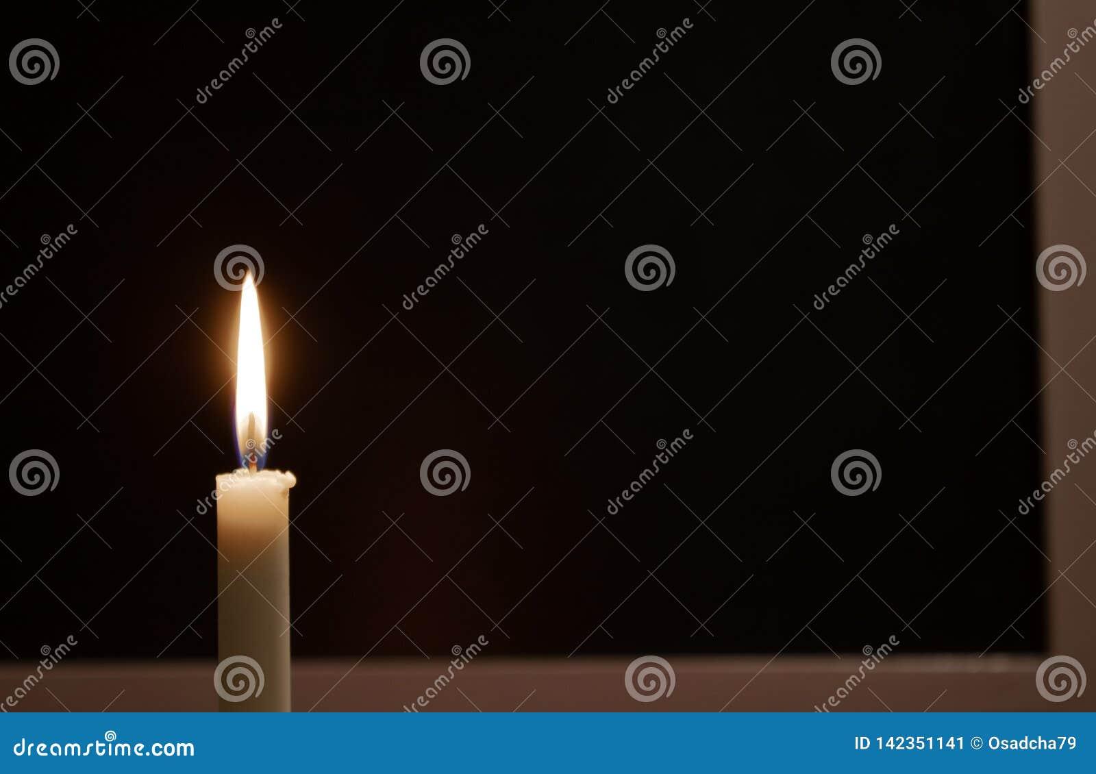 Vela ardente branca em um fundo preto Lamentando, vela ardente