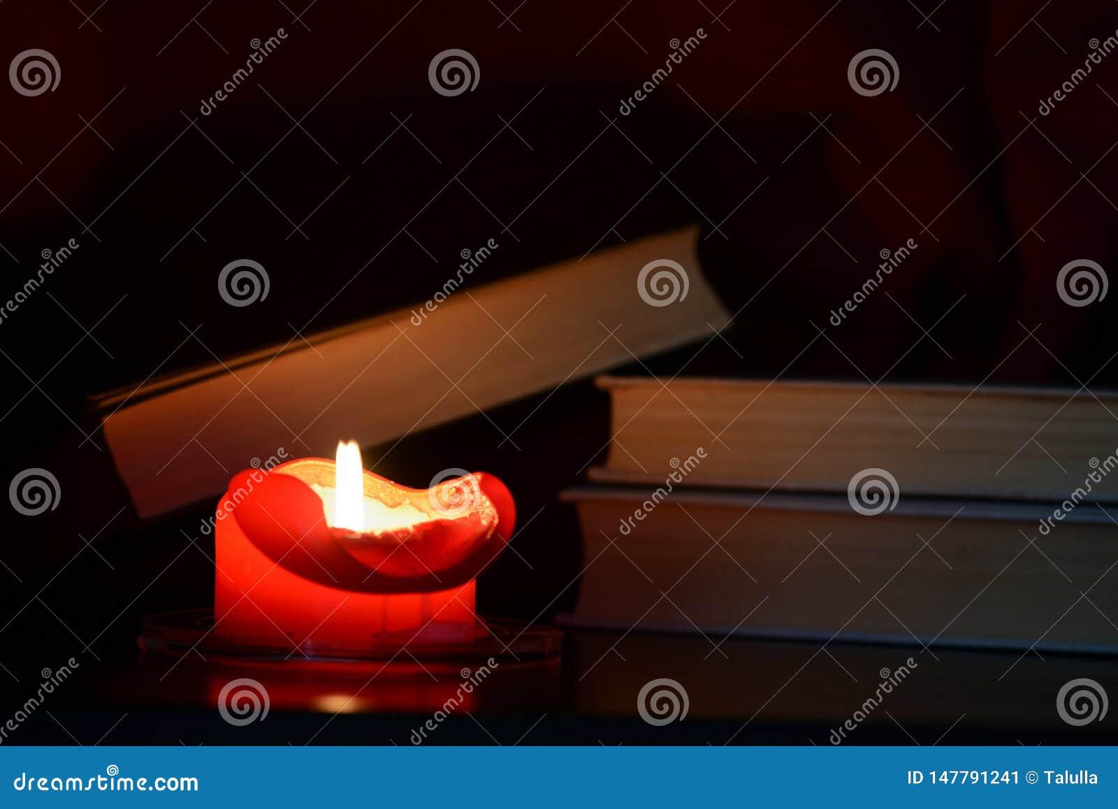 Vela ardente vermelha e livros velhos na obscuridade