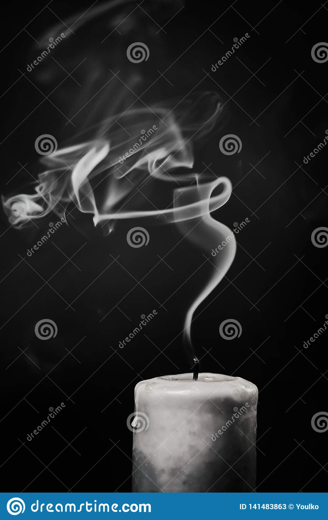 Vela blanca extinta con humo en un fondo negro