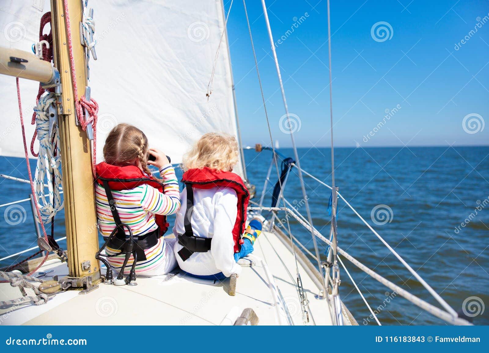 Vela de los niños en el yate en el mar Navegación del niño en el barco