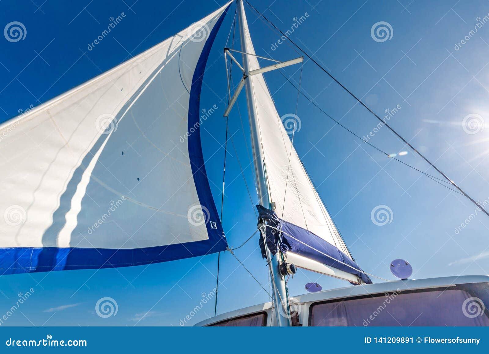 Vela de um barco de navigação contra o céu com raios do sol