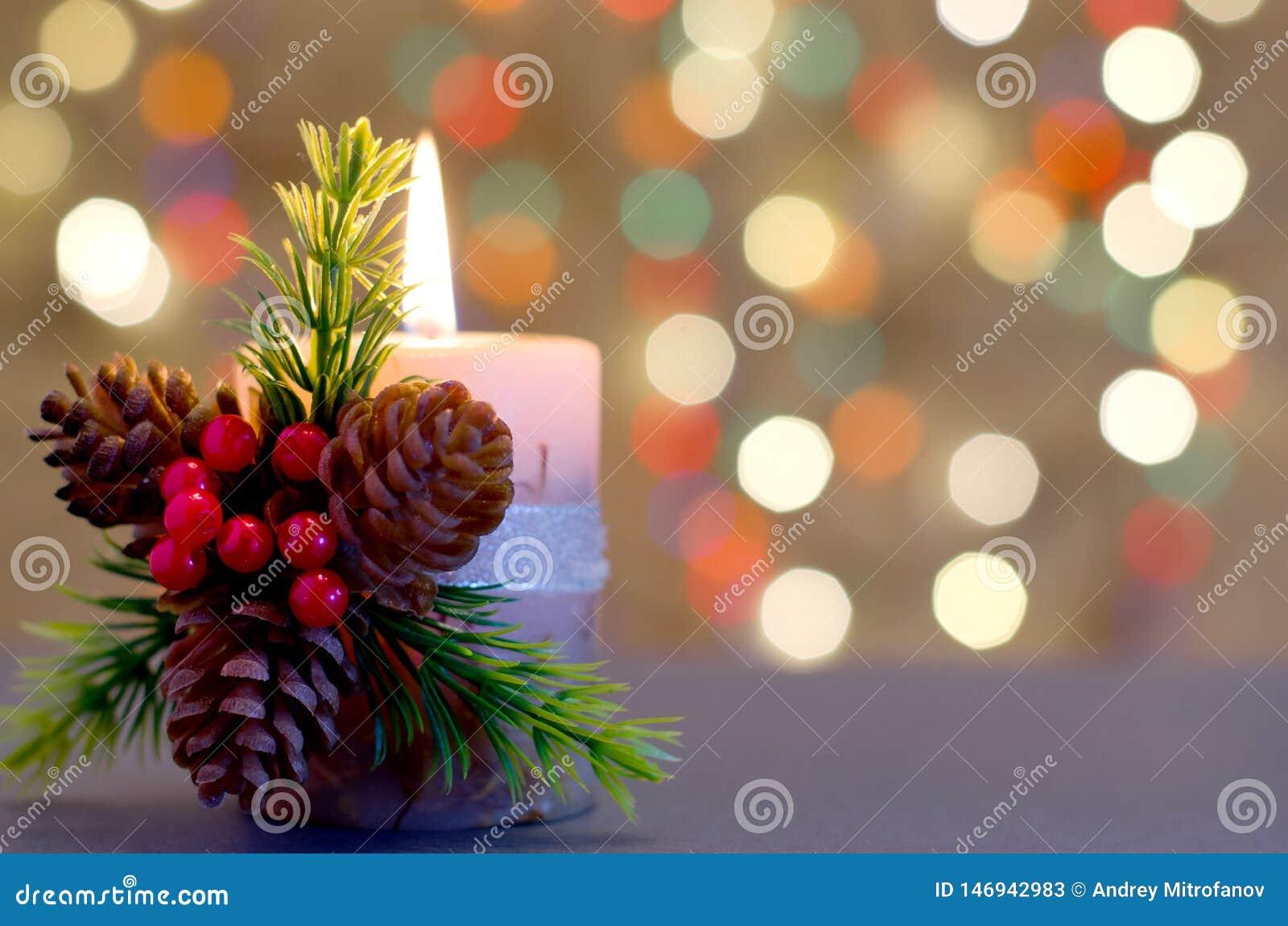 Vela decorativa con las bayas y los conos
