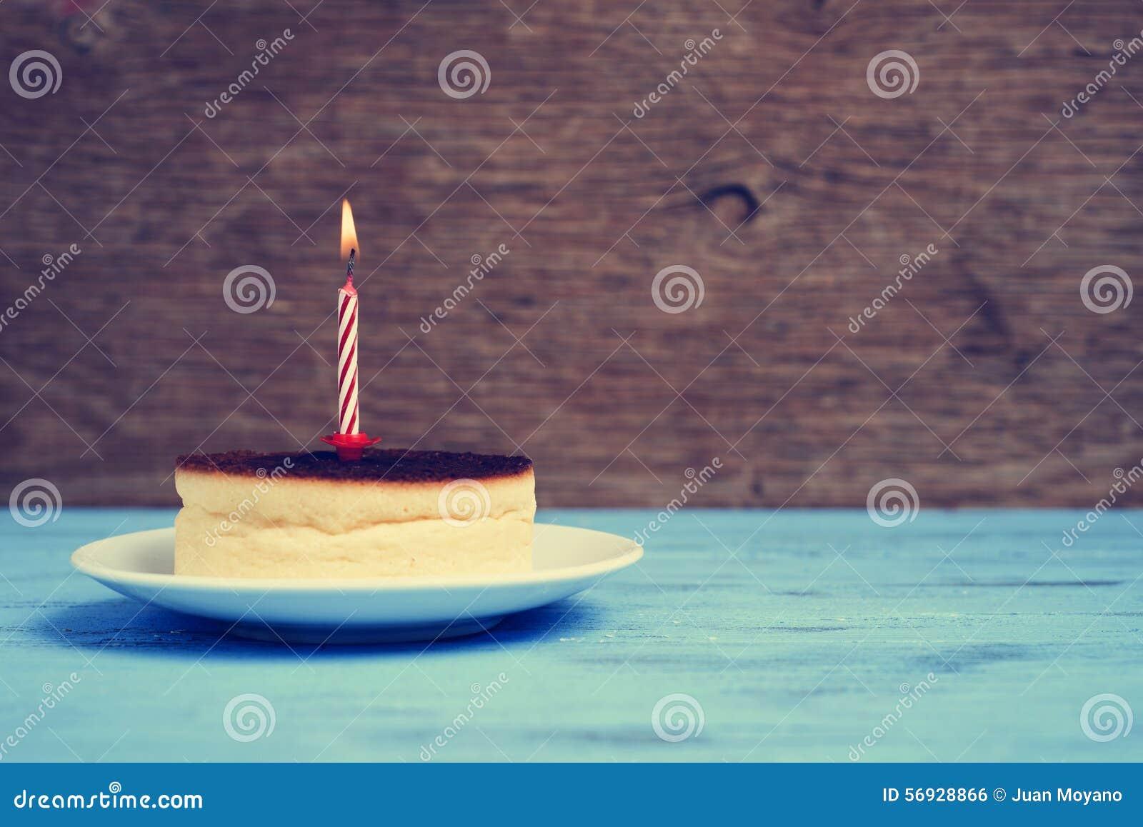 Vela encendida del cumpleaños en un pastel de queso, con un efecto retro
