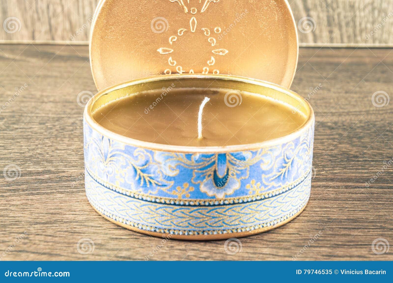 Vela hecha a mano hecha en la caja redondeada de oro adornada con la tela texturizada