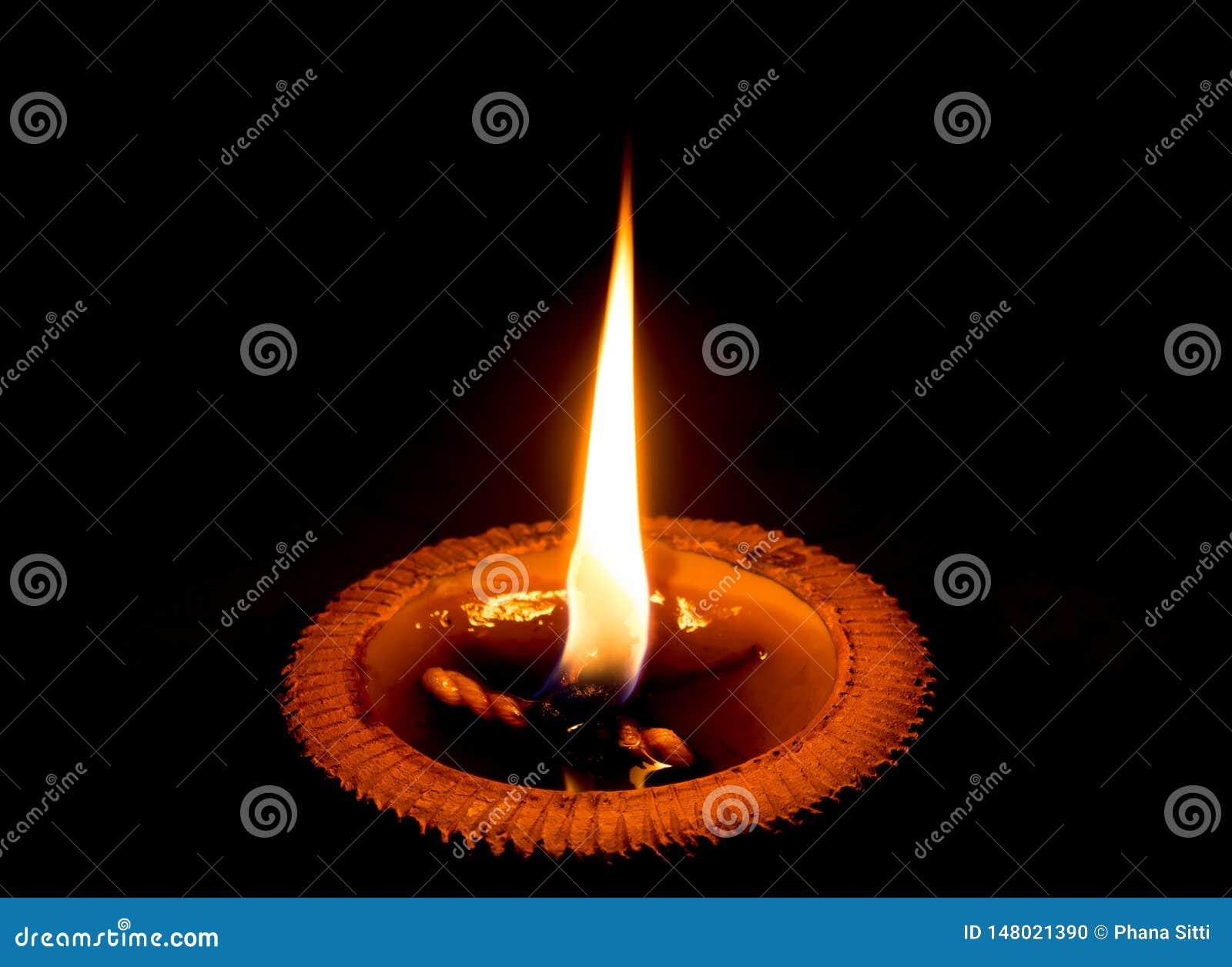 Vela ligera que quema brillantemente en el fondo negro Luz de la vela en una bandeja de la cerámica