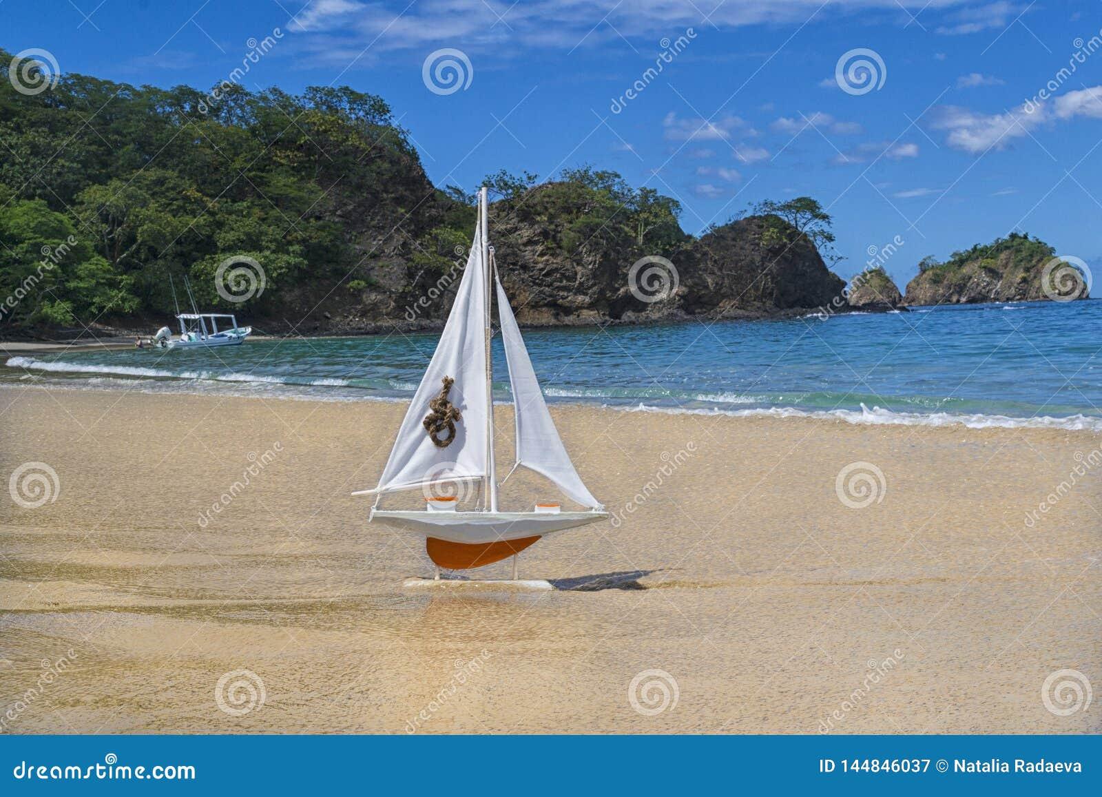 Velas alaranjadas do navio do brinquedo para encontrar aventuras em uma praia bonita