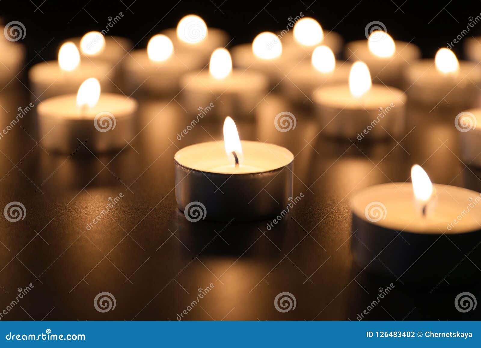 Velas ardentes na tabela na escuridão, close up Fotografia de Stock