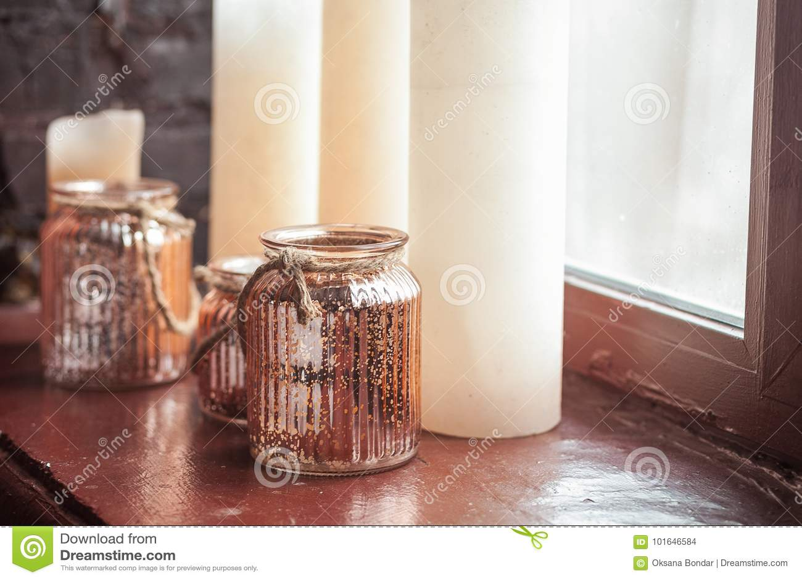 Velas de la Navidad blanca y un tarro de cristal con el travesaño derecho del onwindow de la guita rústica