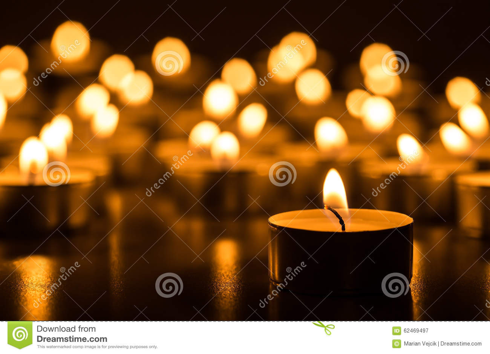 Velas de la Navidad que queman en la noche El extracto mira al trasluz el fondo Luz de oro de la llama de vela