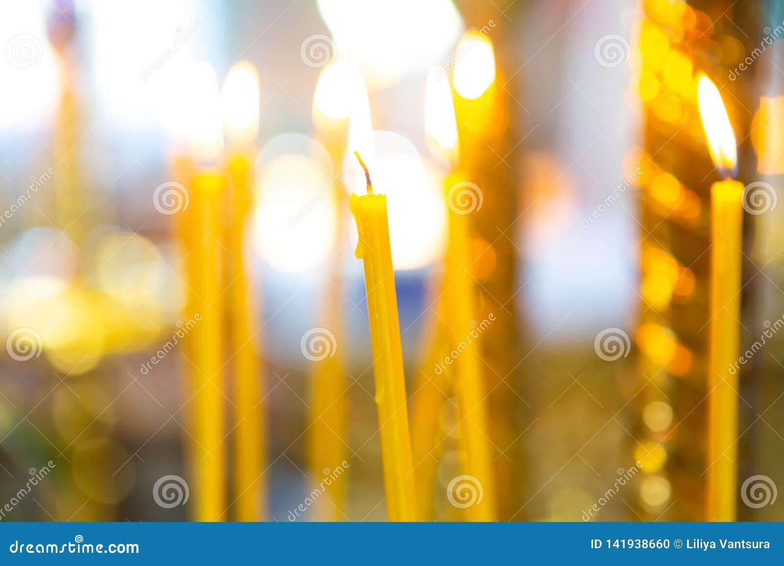 Velas de la quemadura natural de la cera en la iglesia