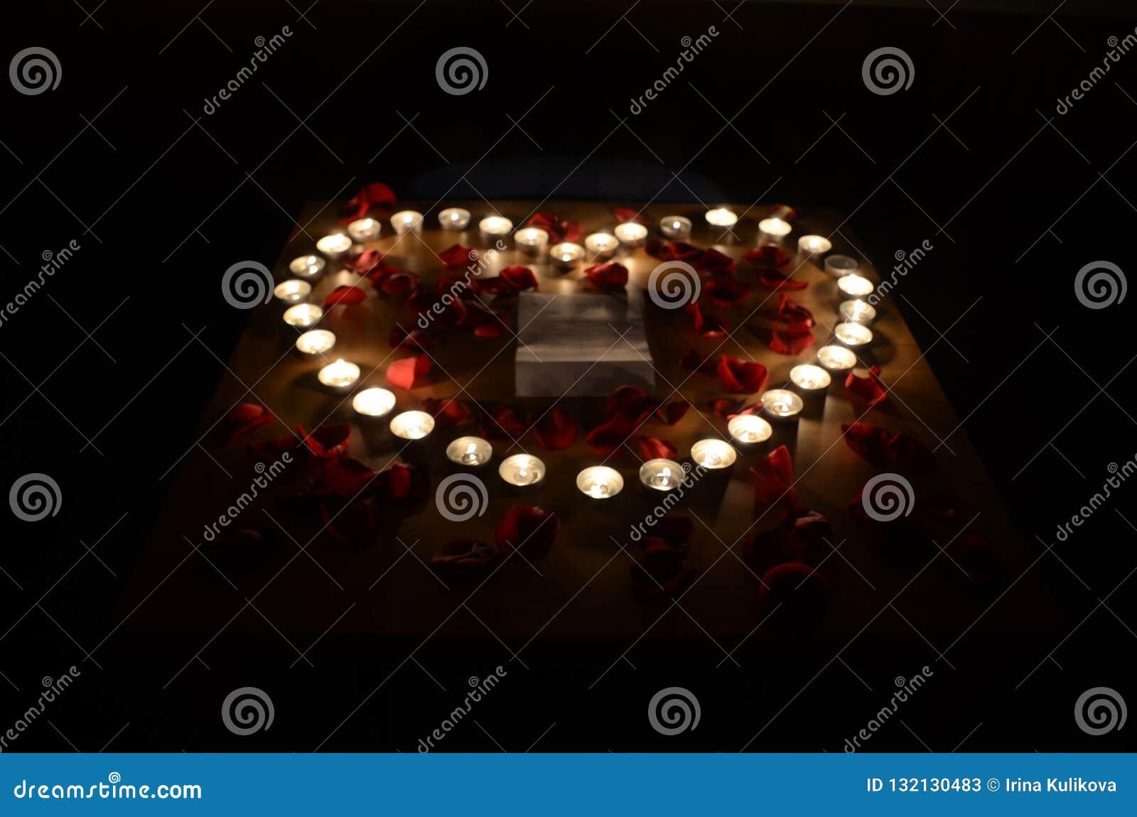 Velas de queimadura no formulário do coração cercado pelas pétalas cor-de-rosa vermelhas em t