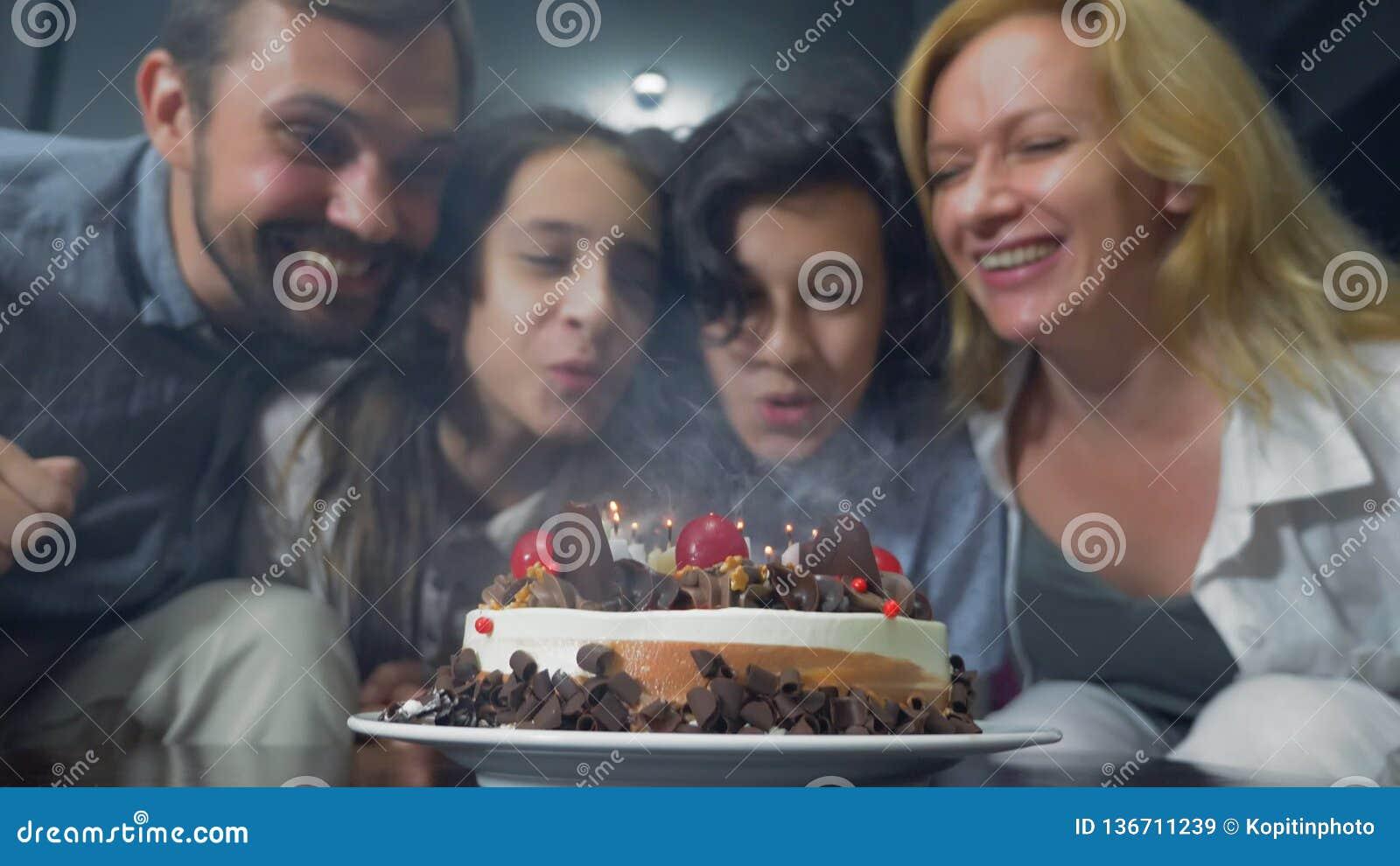 Velas de sopro de sorriso felizes do menino em seu bolo de aniversário crianças cercadas por sua família Bolo de aniversário com