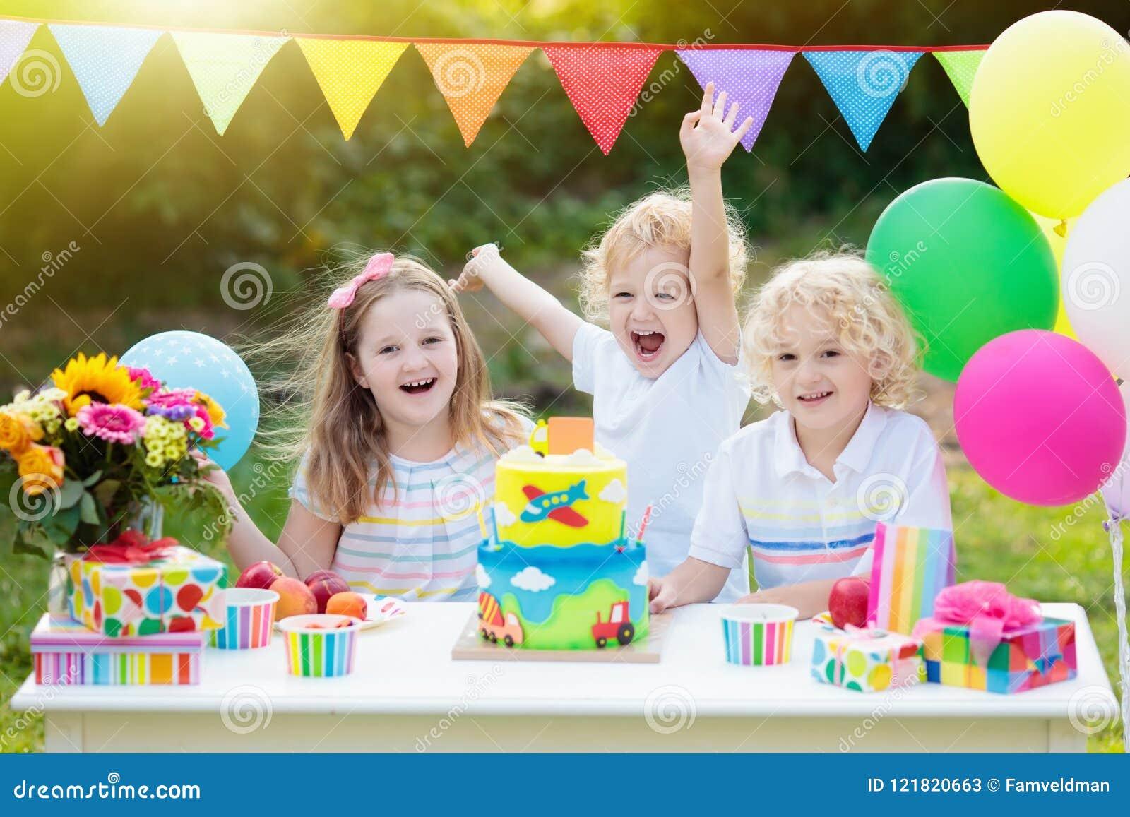 Velas del soplo de los niños en la torta de cumpleaños Partido de los niños