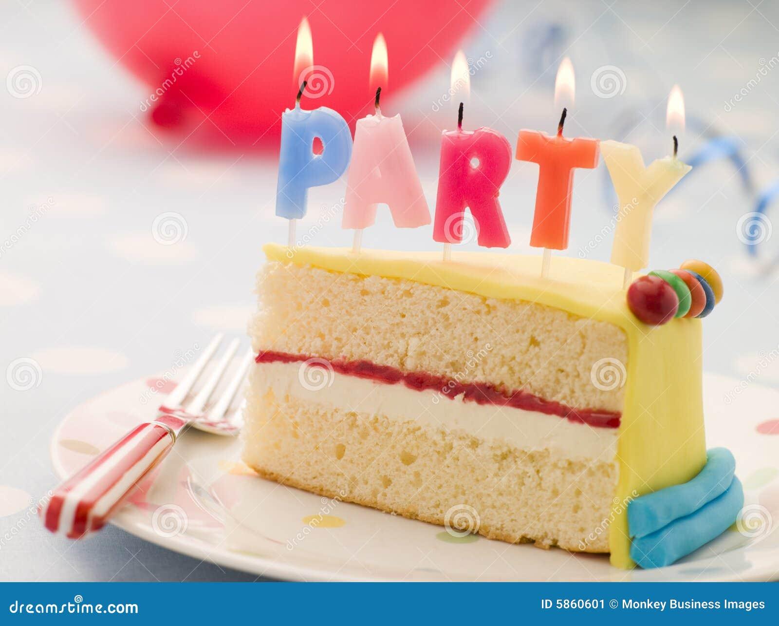 Velas do partido em uma fatia de bolo de aniversário