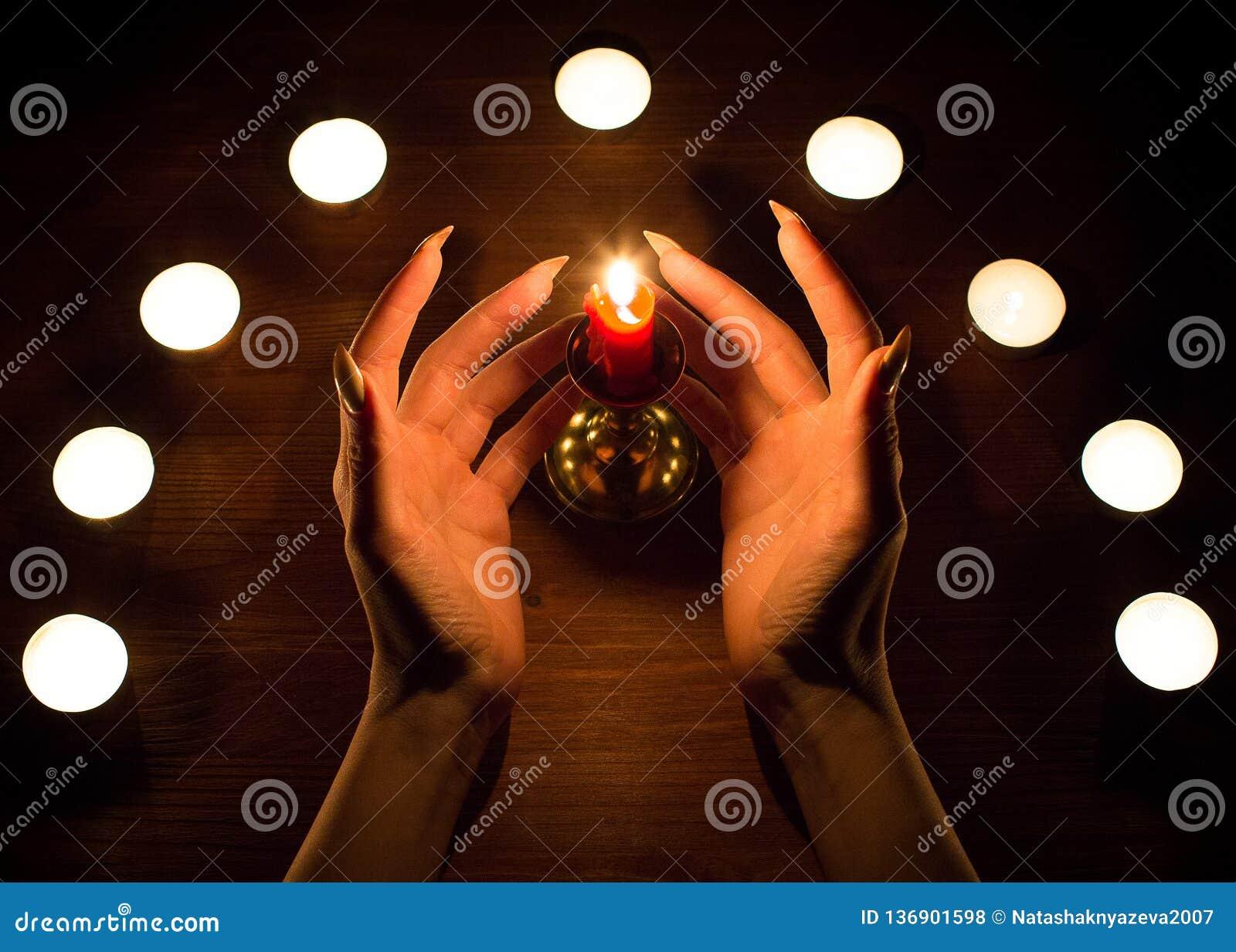 Velas e mãos fêmeas com pregos afiados Adivinhação e feitiçaria, baixa chave