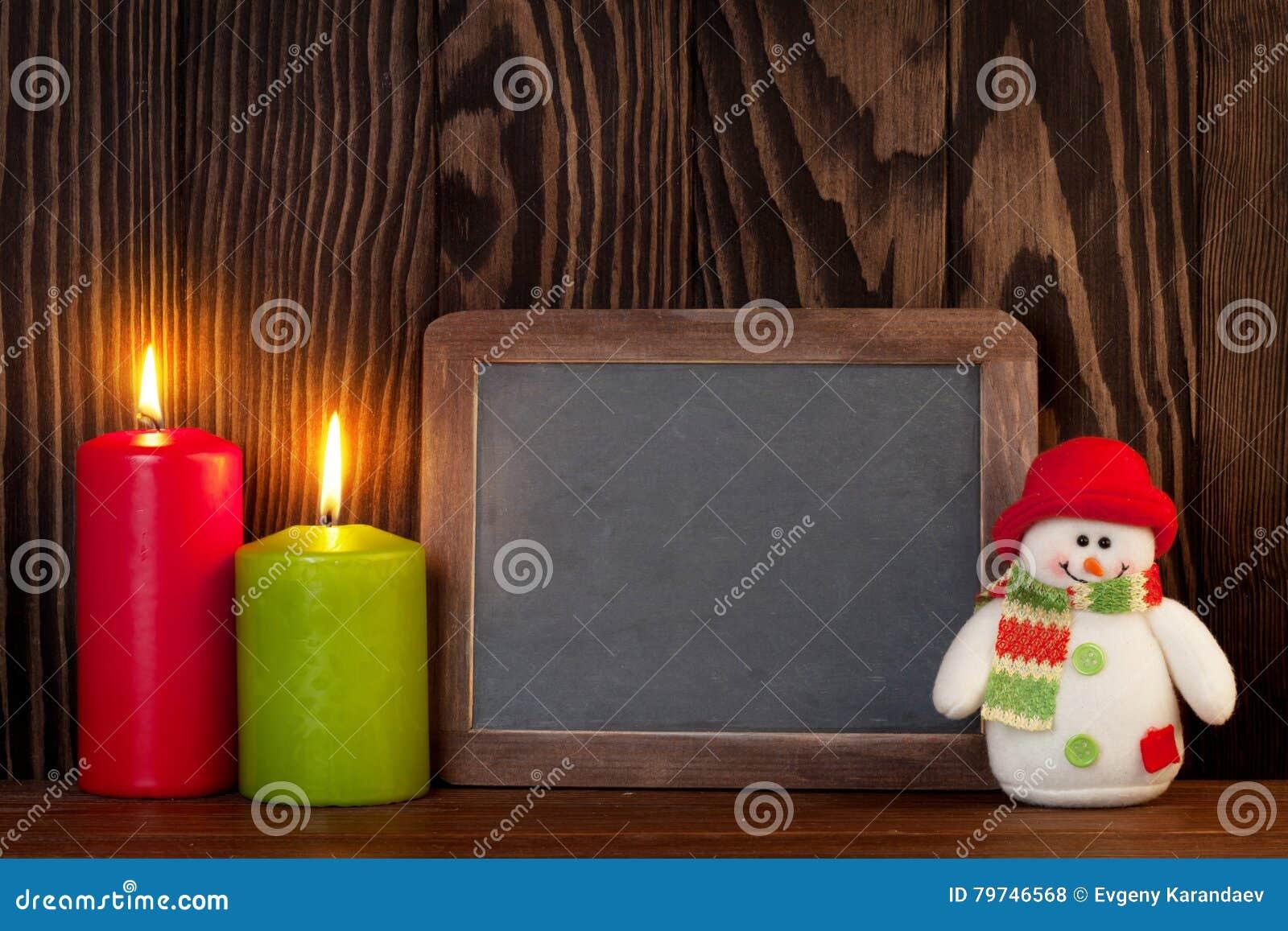 Velas, muñeco de nieve y pizarra de la Navidad