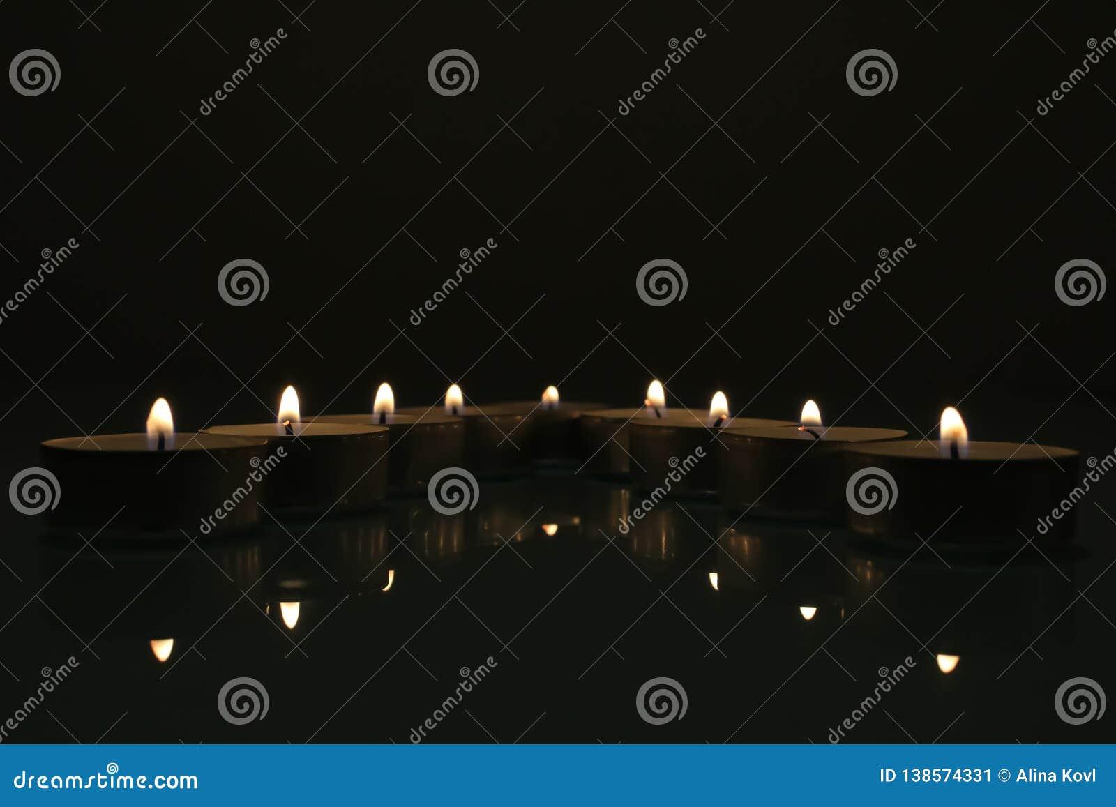Velas que queman en la obscuridad Grupo de velas en la oscuridad