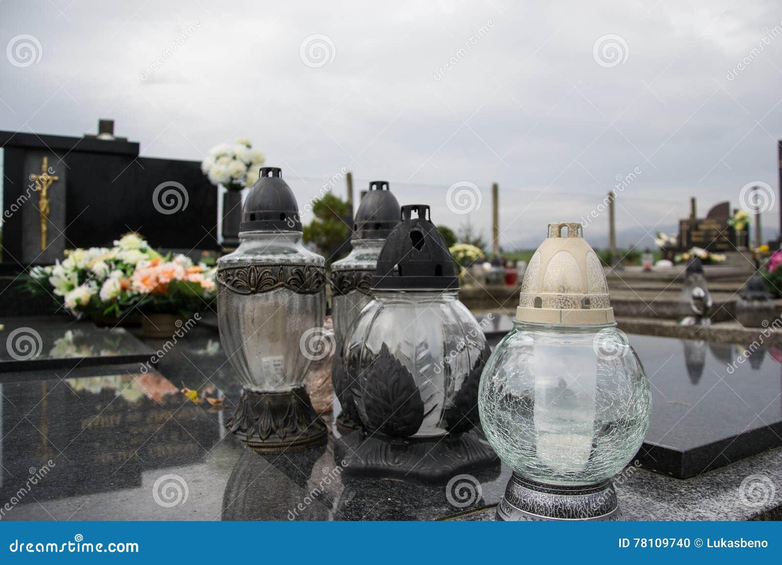 Velas votivas da lanterna na sepultura no cemitério eslovaco Todo o Saints& x27; Dia Solenidade de todos os Saint Tudo Hallows a