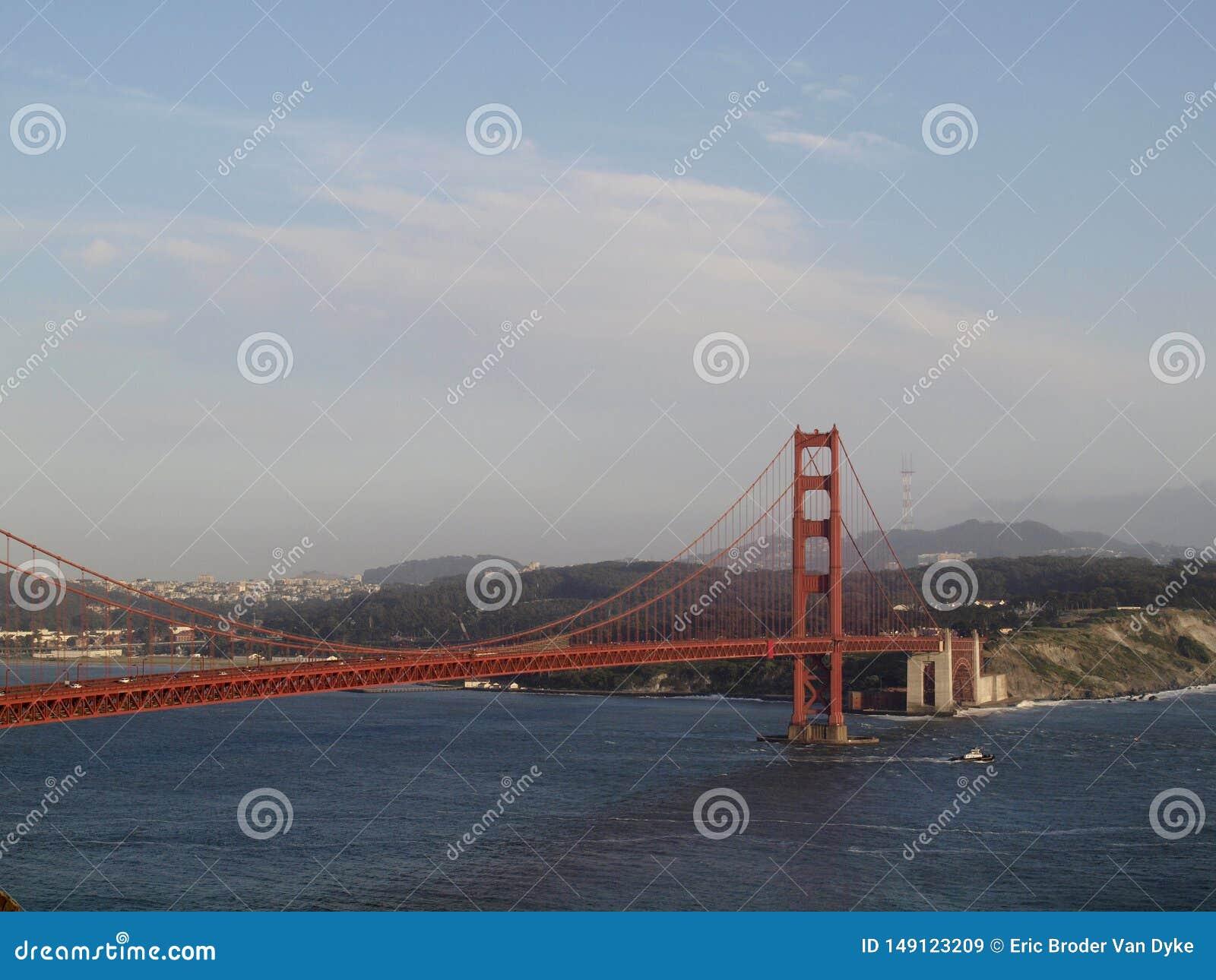 Vele della barca del rimorchiatore sotto golden gate bridge con San Francisco Cityscape