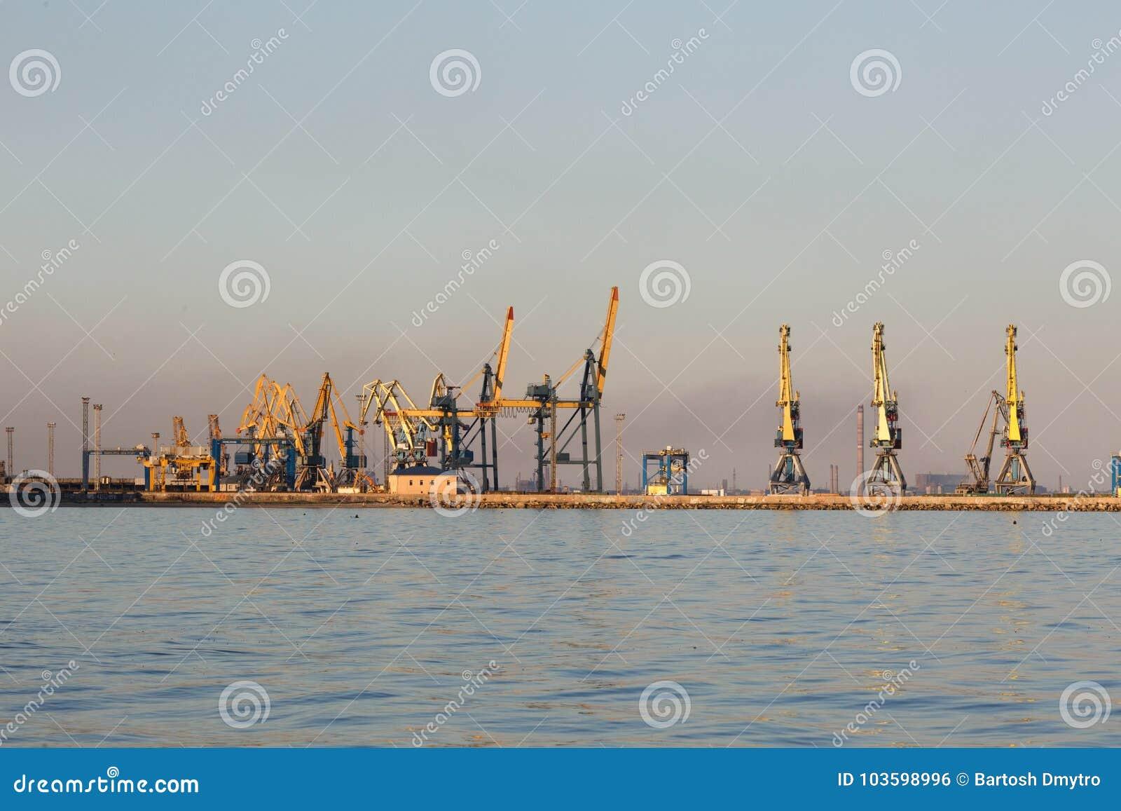 Vele grote kranen silhouetteren in de haven bij gouden licht van zonsondergang Mariupol, de Oekraïne