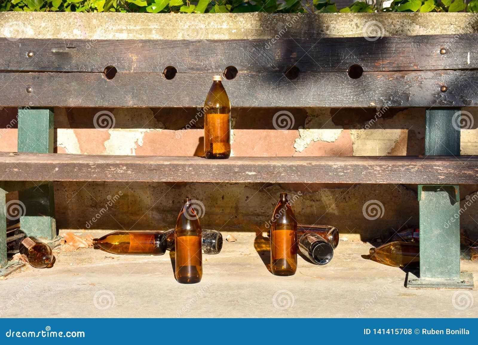Vele grote oranje die flessen bier van glas volledig leeg bij het park toe te schrijven aan somebody wordt gemaakt heeft dronken