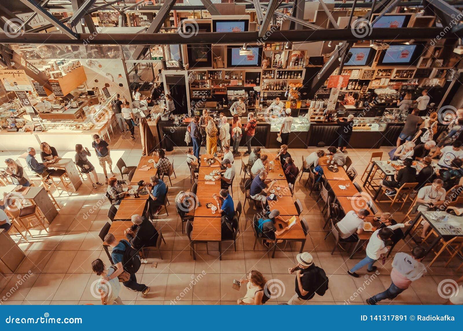 Vele mensen die en het binnen centrale hof van het markt snelle voedsel, met exotische maaltijd drinken eten winkelen