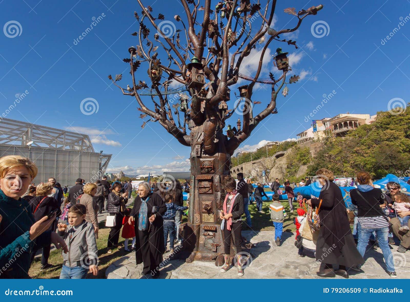 Vele mensen met families die in Rike lopen parkeren met metaalboom van het Leven