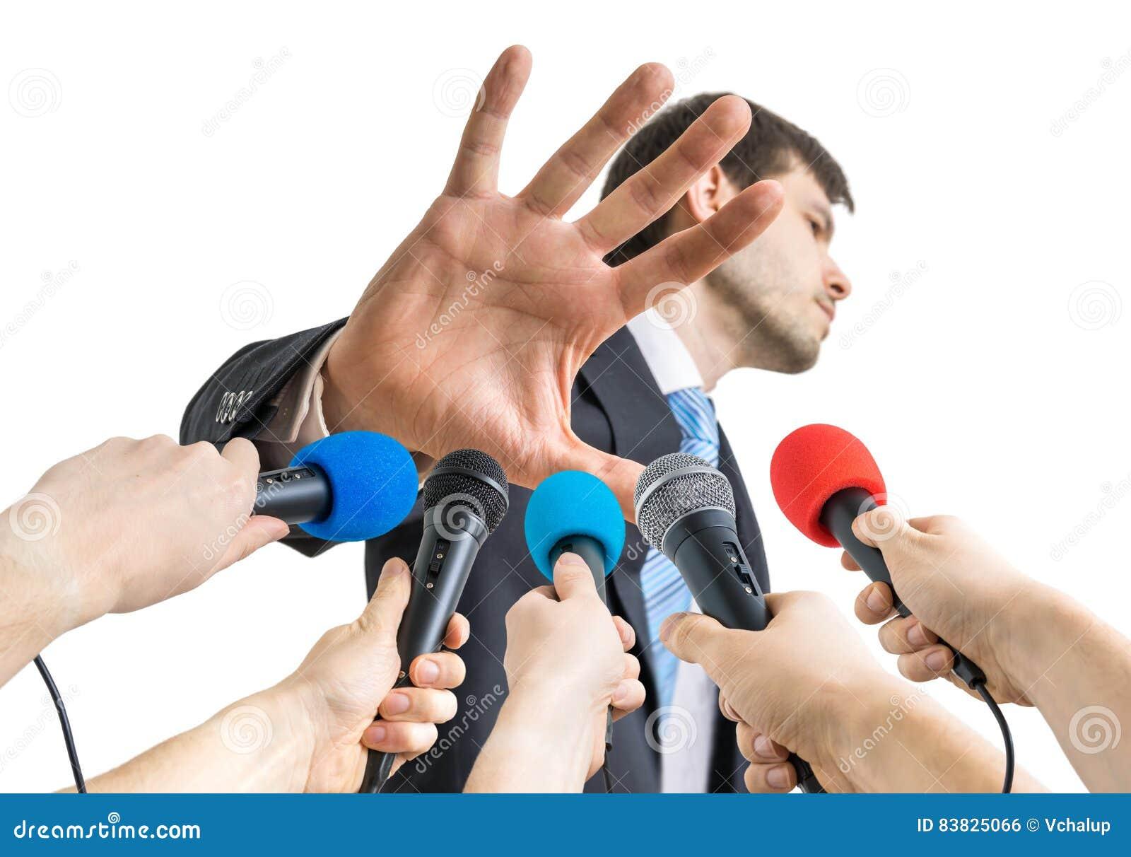 Vele microfoons voor politicus die geen commentaargebaar toont