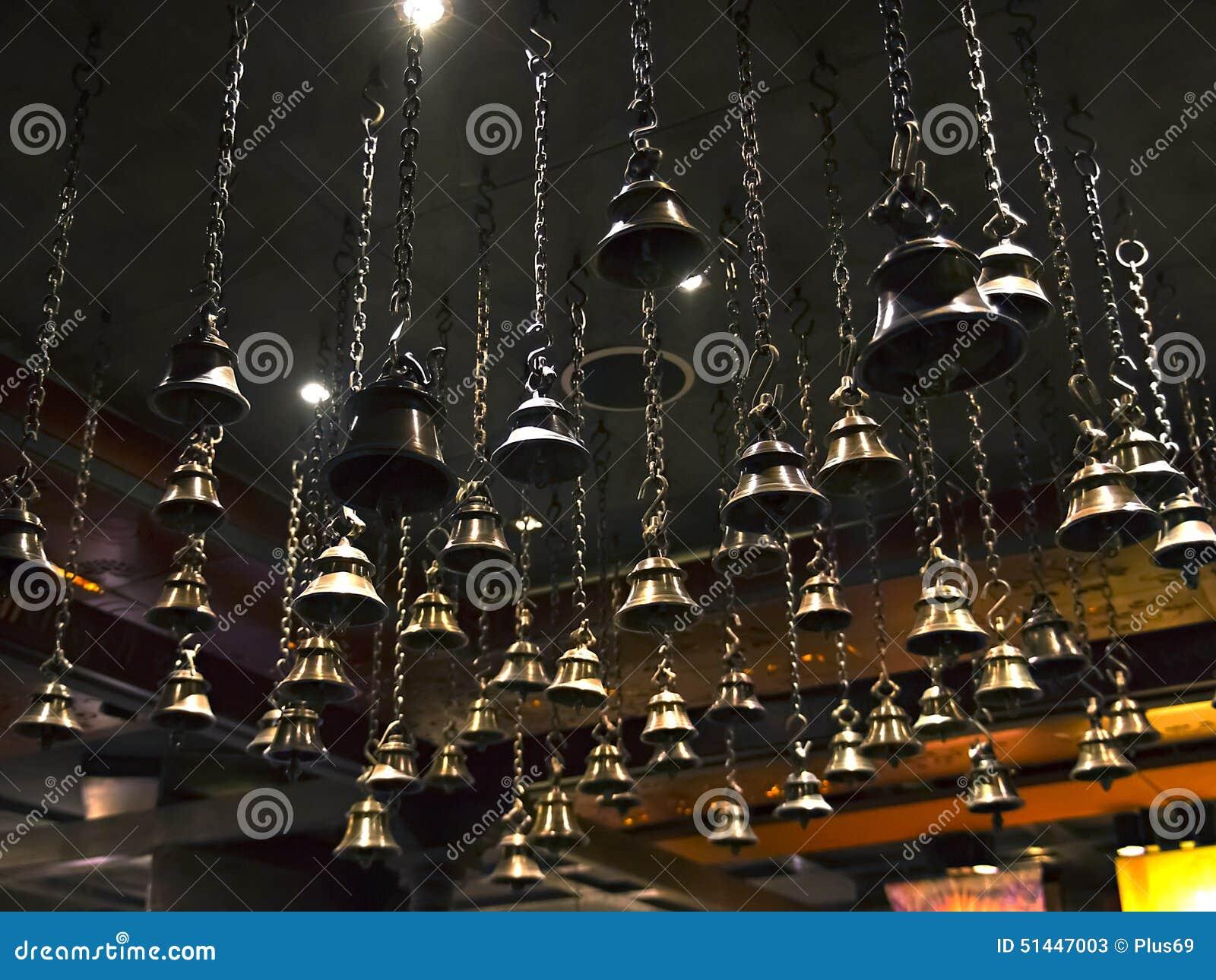 Vele rituele klokken die op kettingen van het plafond hangen