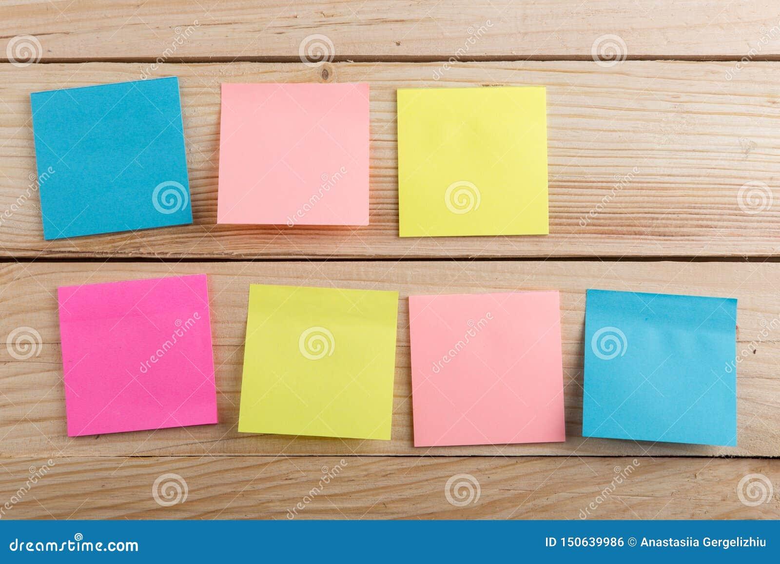 Velen kleurrijke kleverige nota over houten bureau De ruimte van het exemplaar