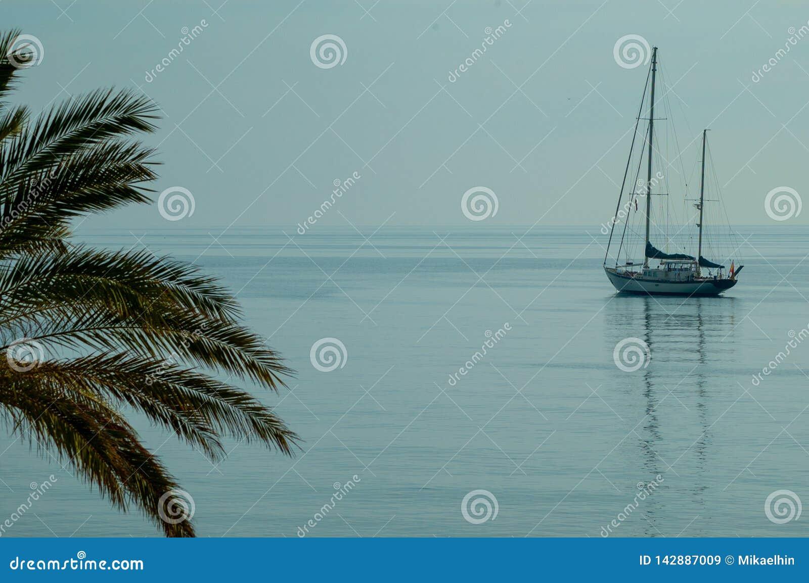Velero solo en el mar Mediterráneo, paisaje de la tranquilidad en un mar