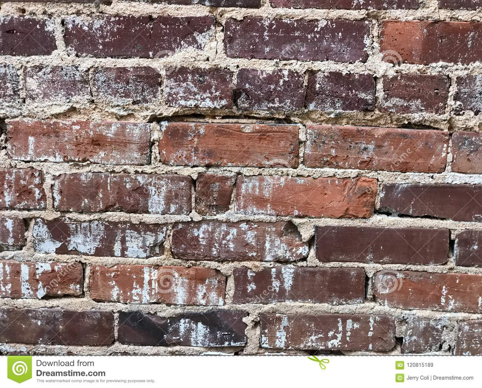 Velho advirta abaixo da parede de tijolo com failing do cimento