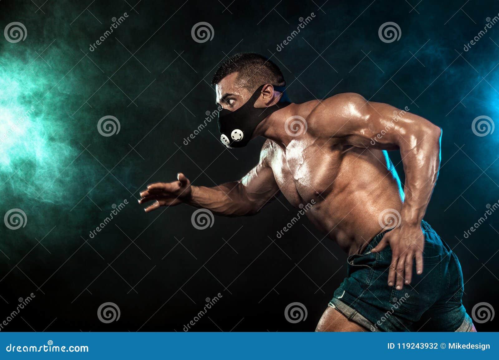 Velocista atlético forte do homem na motivação da máscara, do corredor, da aptidão e do esporte do treinamento Conceito do corred