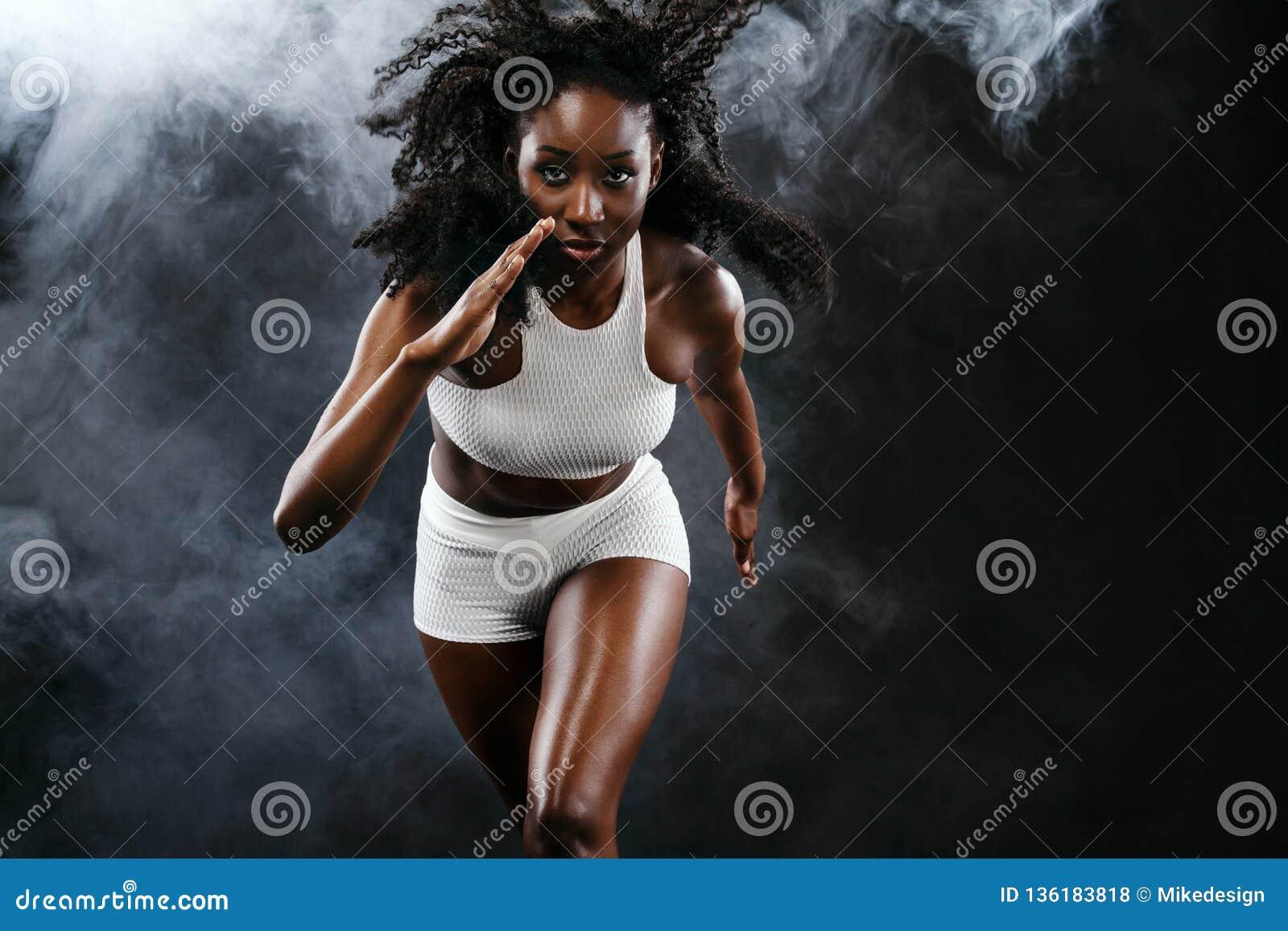 Velocista preto atlético forte da mulher da pele, correndo no fundo com o fumo que veste no sportswear Aptidão e esporte