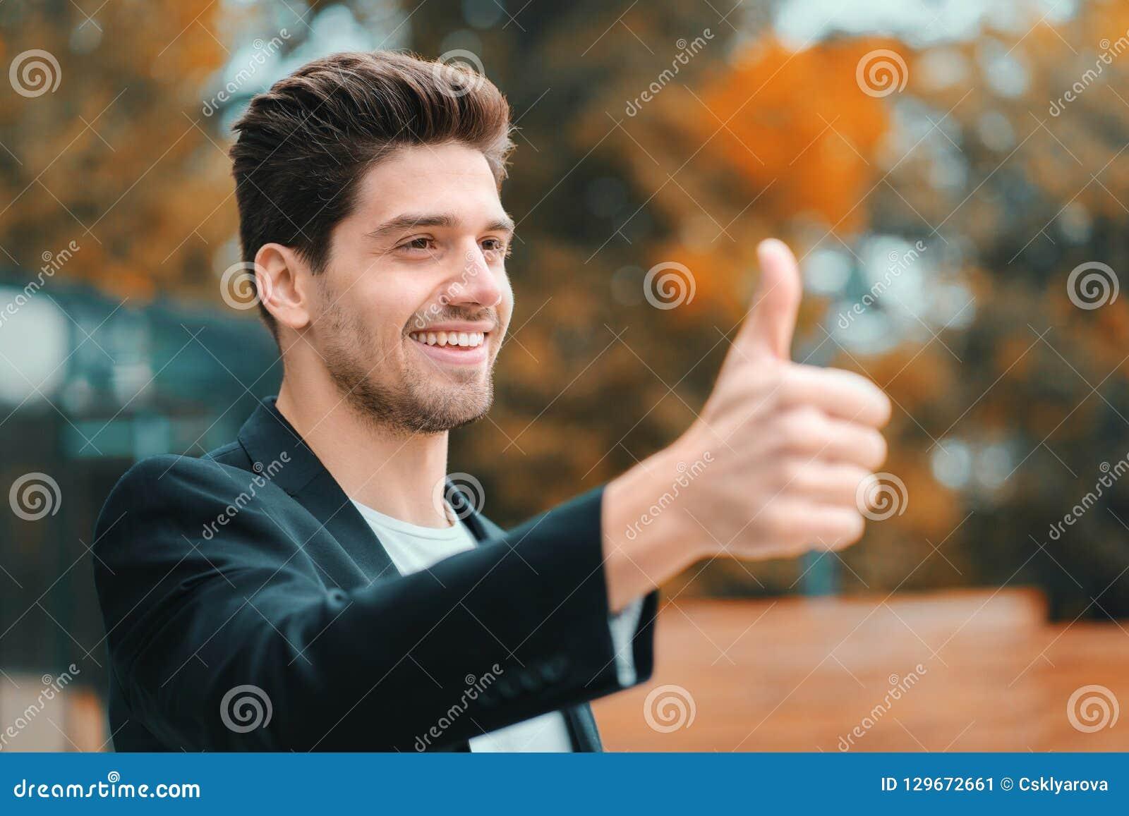 Vencedor Sucesso O homem novo moreno na roupa do negócio no distrito de escritório sorri à câmera e dá os polegares acima feliz