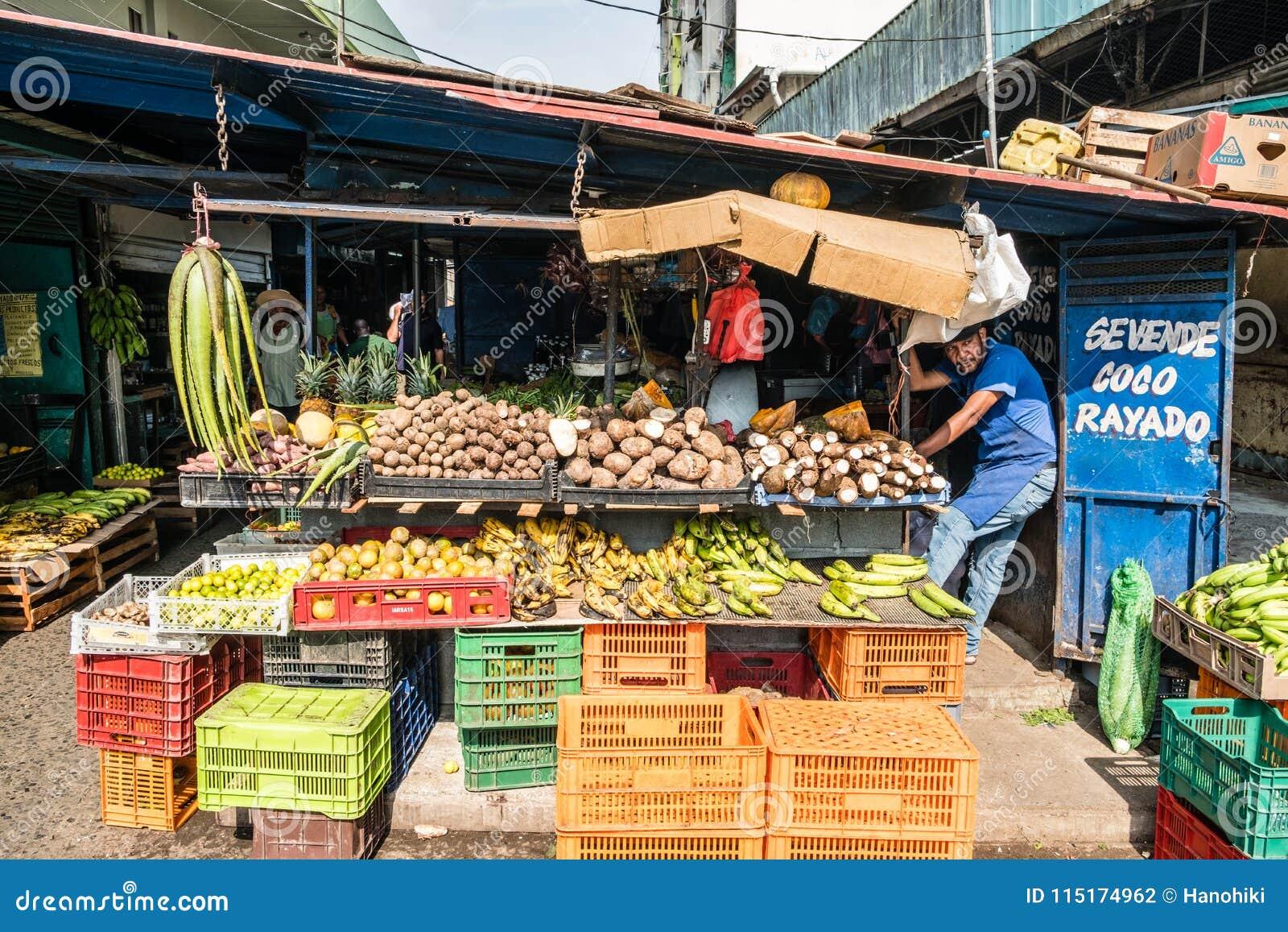 Vendedor das frutas e legumes no mercado do alimento no CEN de Avenida da rua