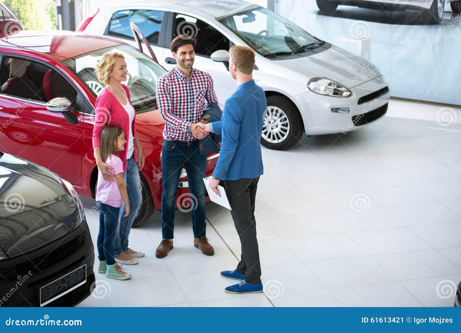 Vendedor de coches que muestra el nuevo vehículo a los clientes
