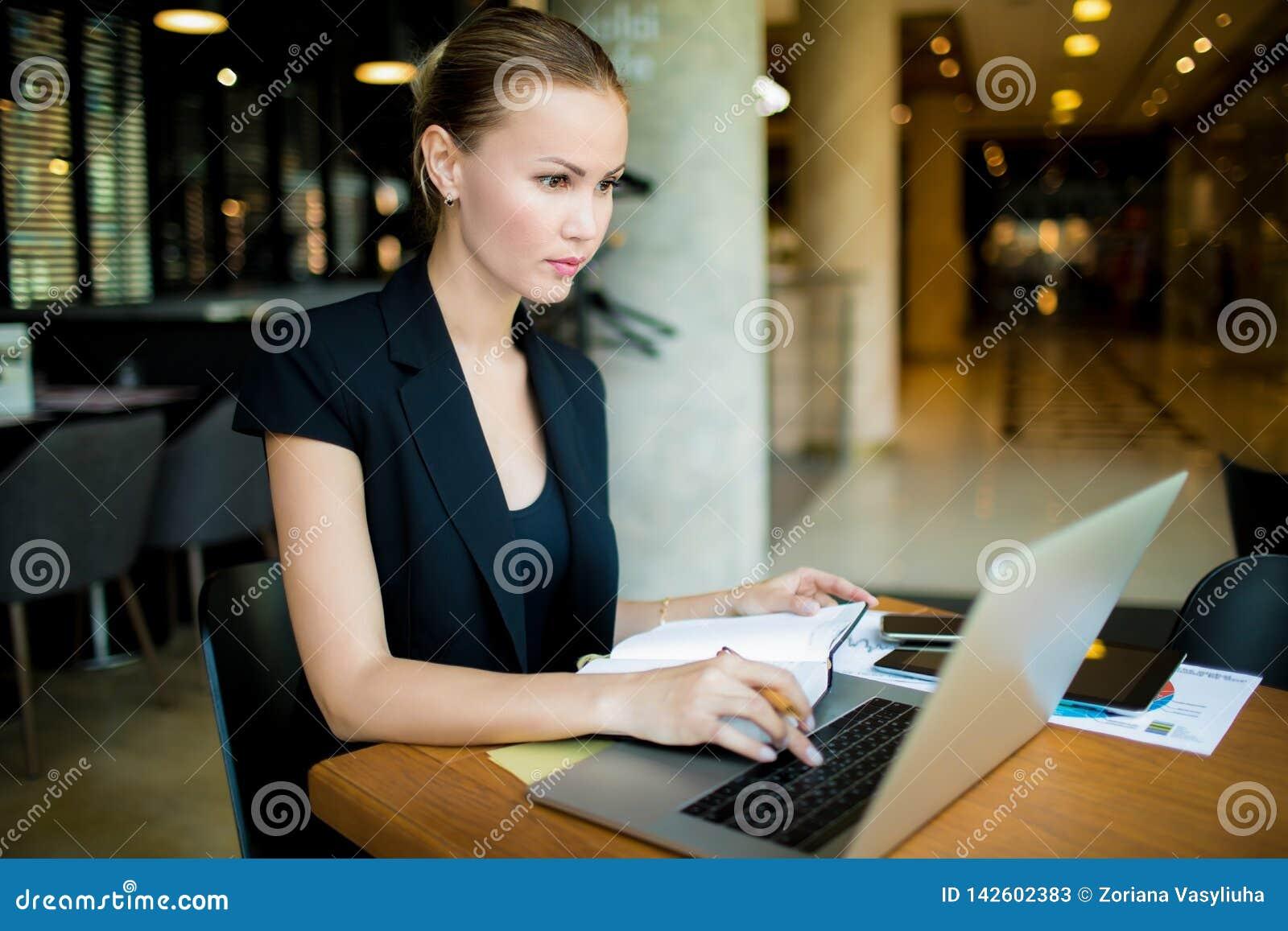 Vendedor de la mujer que busca la información sobre el entrenamiento común vía el ordenador portátil