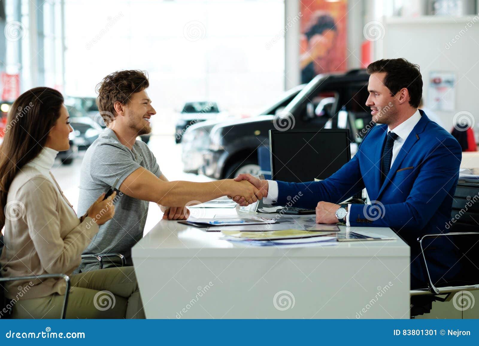Vendedor e cliente que agitam as mãos que felicitam-se na sala de exposições do negócio
