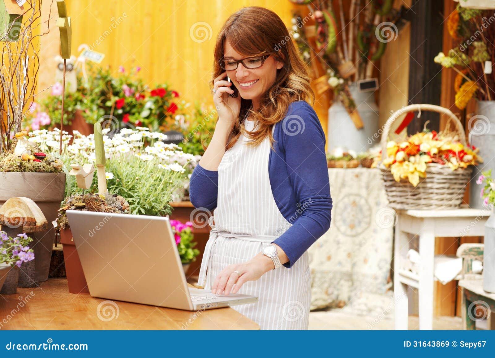 Vendedor maduro de sorriso de Small Business Flower do florista da mulher