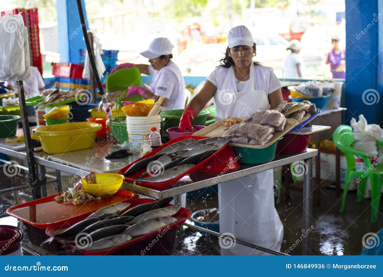 Vendedor peruano f?mea em um mercado do marisco dos peixes